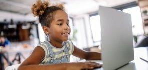 Menina usa computador para acompanhar aula do ensino remoto