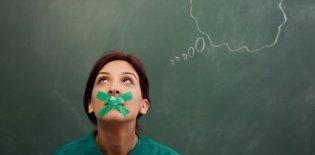 Uma professora com adesivo na boca olhando para cima. Na lousa atrás dela está desenhando um balãozinho de pensamento saindo de sua cabeça