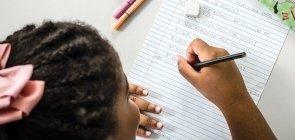 Imagem de cima em que aluna escreve em seu caderno
