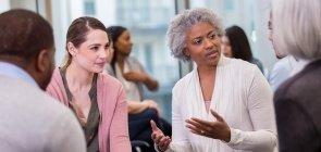 Mulher negra de cabelo branco, conversa com pequeno grupo