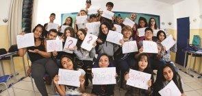 Grupo de alunos mostram com cartazes escrito sim, não ou um ponto de interrogação