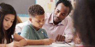 Professor ajuda aluno em sala de aula