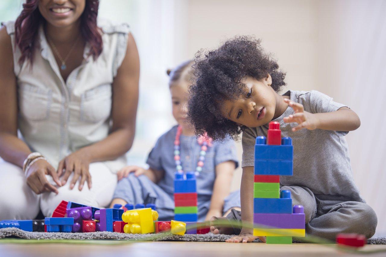 Crianças brincam com peças coloridas em cima de uma mesa observadas por uma mulher adulta