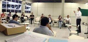 Sala de aula com carteiras dispostas em U ocupadas por adultos e professor no centro