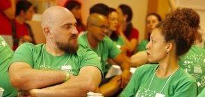 um homem forte, branco e careca de camiseta verde e braços cruzados diante do corpo olha com um semblante sério para sua colega sentada na cadeira ao lado, negra de cabelos presos e blusa também verde, que retribui o olhar