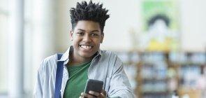 Estudante segura celular na mão dentro da escola