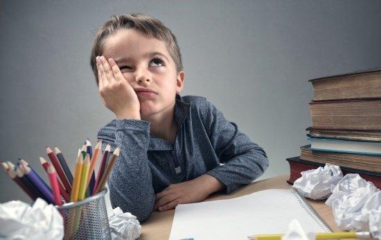 Criança triste apoiada na mesa com várias folhas de papel amassadas