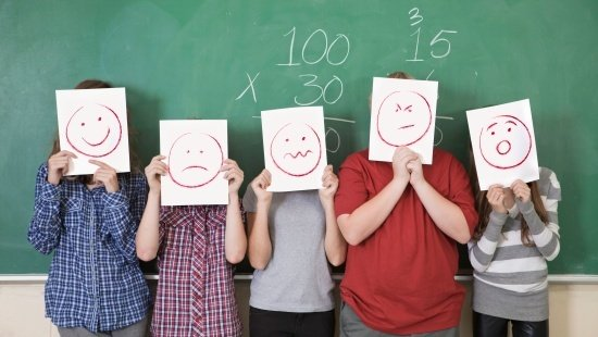 Cinco crianças em frente a uma lousa segurando desenhos de carinhas com diferentes expressões: feliz, triste, angustiado, irritado, surpreso