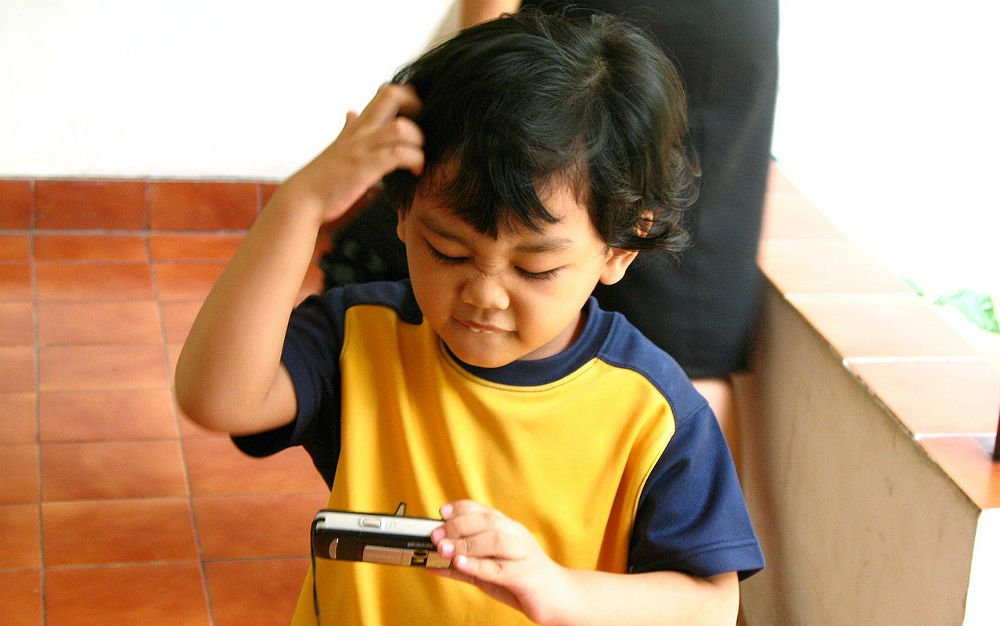 Criança de camiseta amarela e azul olhando para o celular com cara de confusa, coçando a cabeça
