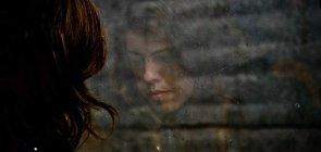 Mulher com depressão junto à janela
