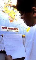 Aluno lê uma mensagem diante do mapa-múndi: alfinetes coloridos para marcar localizações que rendem atividades bastante curiosas Foto: Massao Gotto Filho
