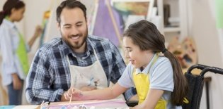 Em uma sala de aula, menina em cadeira de rodas faz uma pintura em uma mesa, auxiliada por um professor de avental