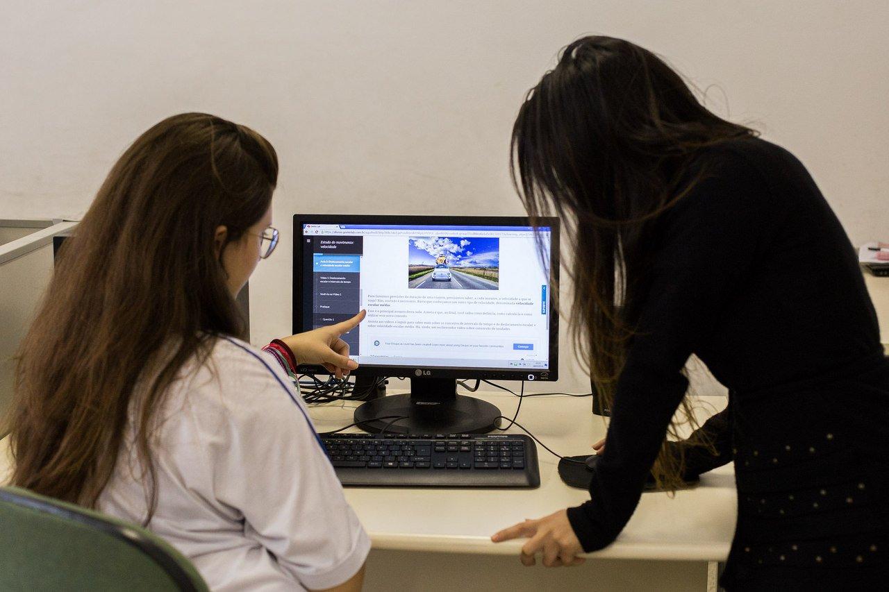 Duas mulheres de costas, uma de pé e outra sentada, olham a tela de um computador (Crédito: Diogo Moreira/A2 FOTOGRAFIA)