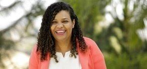 Uma mulher negra de cerca de 35 anos sorrindo