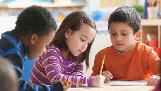 Três crianças sentadas em grupo. A menina ao centro escreve enquanto seus dois colegas observam