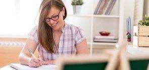 Professora escreve bilhete para pais de alunos sentada na sala de aula