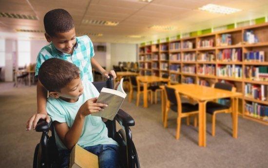 Imagem ilustrativa de menino com deficiência física na biblioteca da escola, com um colega