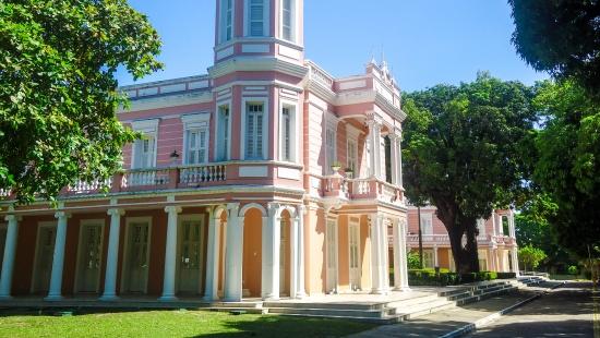 Prédio clássico de fachada rosa com detalhes brancos e entrada em L