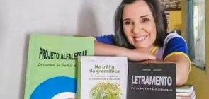 Professora Mirlene sorri para a foto, na frente dela tem livros sobre alfabetização