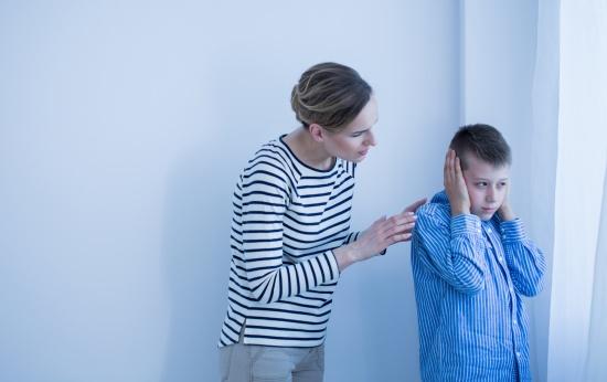 Menino com asperger tampa os ouvidos enquanto a mãe fala com ele.