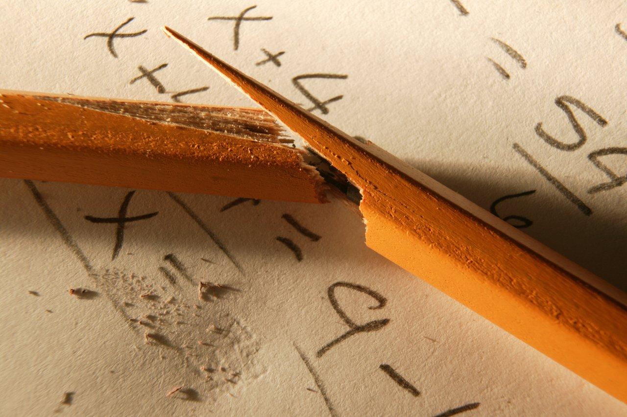 Lápis quebrado em caderno com operações matemáticas