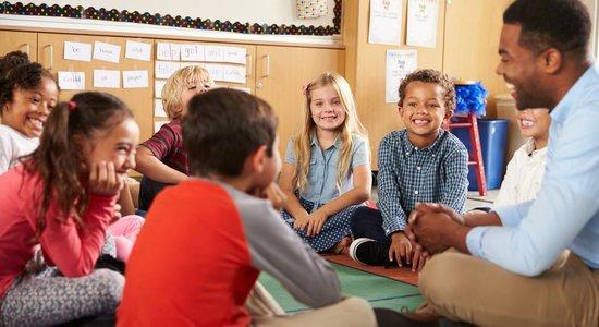 Professor conversa com crianças sentado no chão (Foto: Shutterstock/Monkey Bussiness Images)