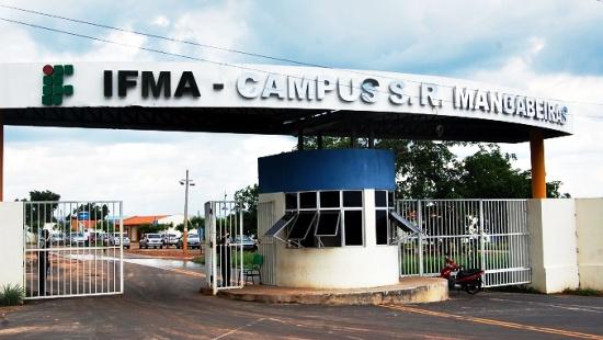 """Dois portões brancos com uma guarita de janelas de vidro no meio deles, protegidos por uma laje em que se lê """"IFMA - Campus S. R. Mangabeiras"""""""
