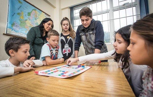 Seis alunos em volta de uma mesa olham concentrados para um tabuleiro. Uma menina mexe uma peça. Uma professora acompanha a atividade