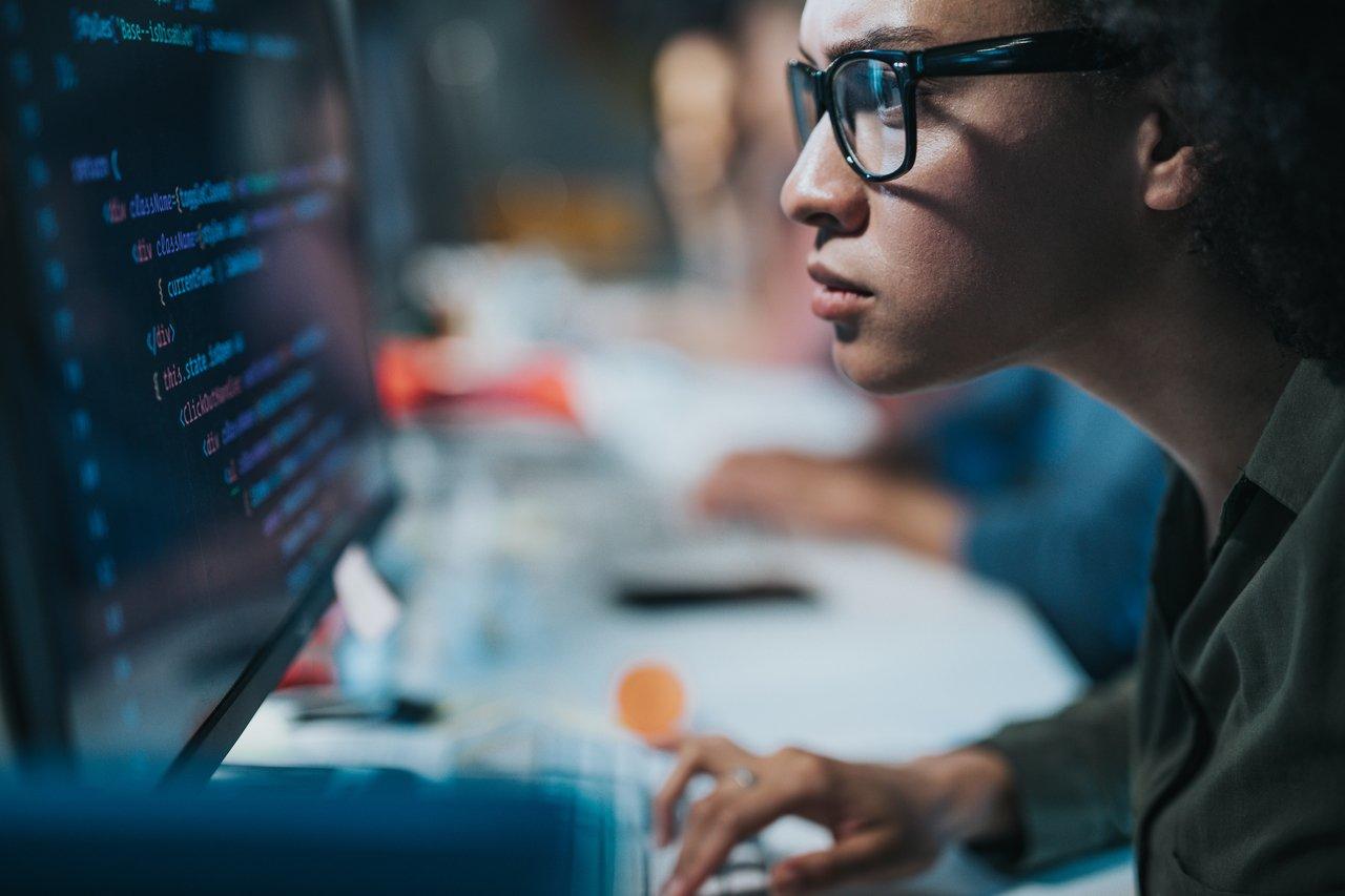 Em uma sala escura, mulher negra está sentada em uma mesa, em frente a um computador, olhando atentamente para a tela e digitando no teclado