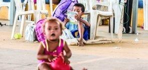 Uma bebê em primeiro plano aparece embaçada com um brinquedo na mão. No fundo, um menino sentado no chão, apoiado numa cadeira desgastada, lê