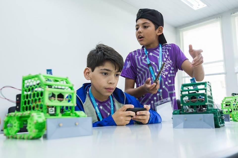 Dois alunos da Escola Municipal Aloys João Mann trabalham com os robôs que construíram