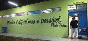 Em uma parede verde lê-se mudar é dificil, mas é possível de Paulo Freire. Ao lado, uma mulher limpa o banheiro masculino