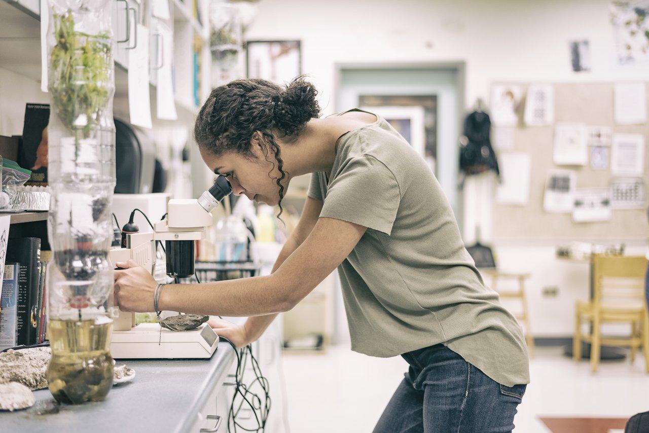 Adolescente do Ensino Médio analisa uma lâmina em um microscópio, em um laboratório de uma escola