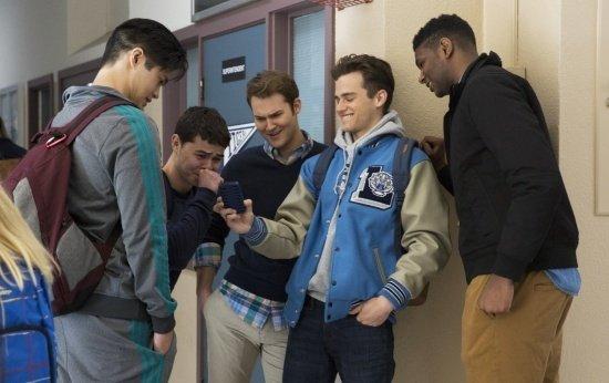 Cena da série13 reasons why em que grupo de jovens vê uma foto em um celular e riem. Crédito: Beth Dubber/Netflix