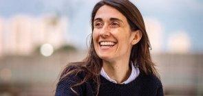 Foto de uma mulher de cabelo comprido e liso, ela sorri olhando para o lado