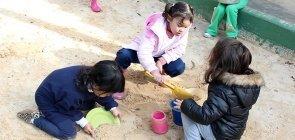 Três crianças de cerca de cinco anos brincando na areia do parquinho