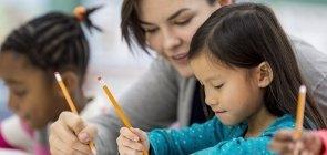 Professora acompanha escrita dos alunos durante aula de Alfabetização