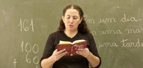 Mara Mansani faz leitura em frente à lousa com uma operação matemática
