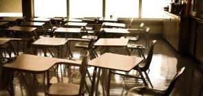 Cadeiras de sala de aula vazias e amontoadas em uma sala com luz indireta