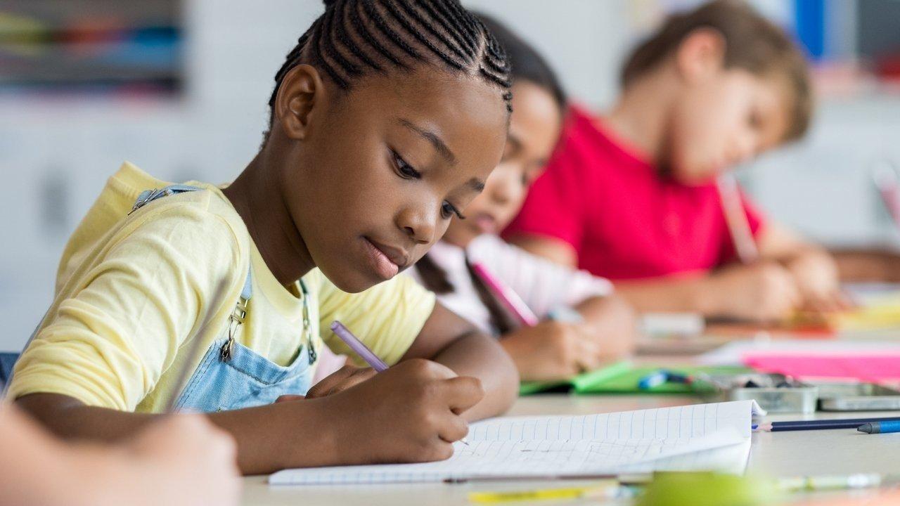 Uma menina negra de cabelo trançado de cerca de 8 anos escrevendo em um caderno sentada em uma carteira escolar