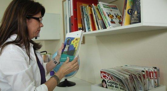 Coordenadora consulta acervo de livros e revistas na escola