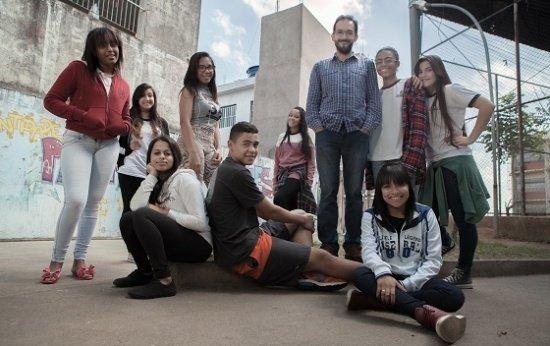 Num espaço externo da escola, o professor Fábio está de pé e ao redor dele, se encontram 9 alunos de cerca de 15 anos.