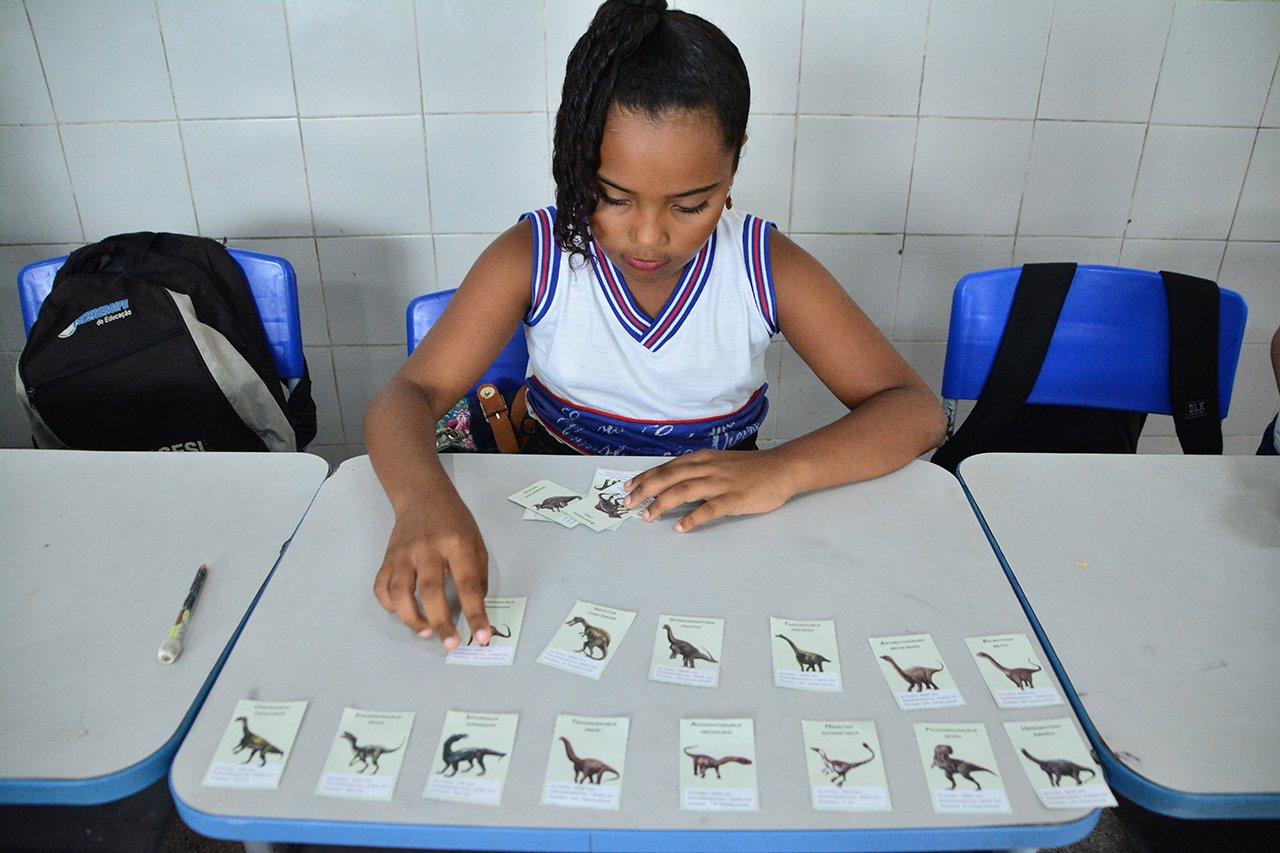 Criança joga Trunfo dos Dinossauros em aula da professora Patrícia Alves Rodrigues, da EE Constâncio Vieira, em Estância (SE)