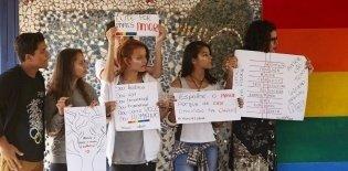 Jovens adolescentes seguram cartazes contra a homofobia. Eles dizem: