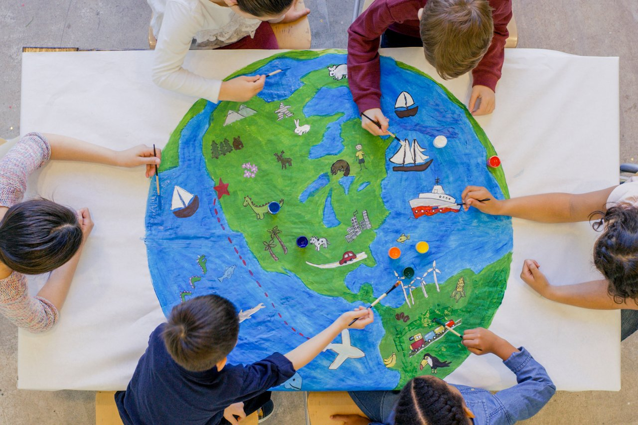Crianças desenham um globo terrestre, vistas de cima