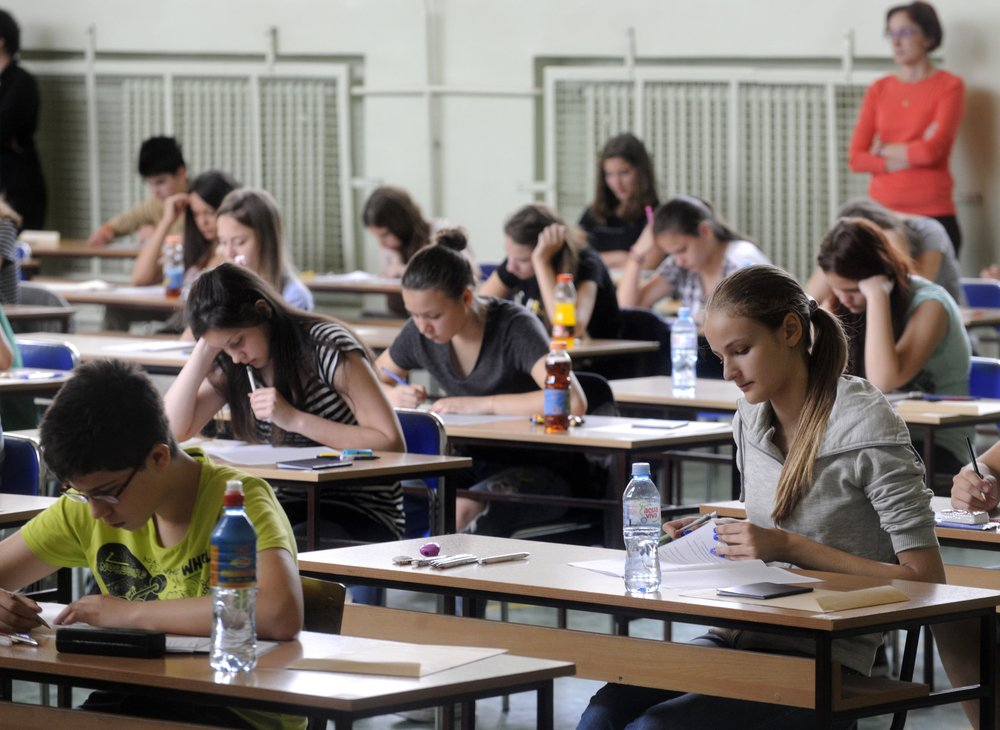 Classe de alunos sentados em suas carteiras fazendo prova