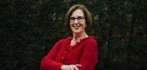 Senhora de 70 anos veste casaco vermelho, ela sorri. No fundo um espaço arborizado