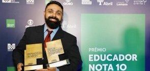 Um homem de barba com cerca de 30 anos segurando dois prêmios, um do Educador Nota 10 e outro de Educador do Ano