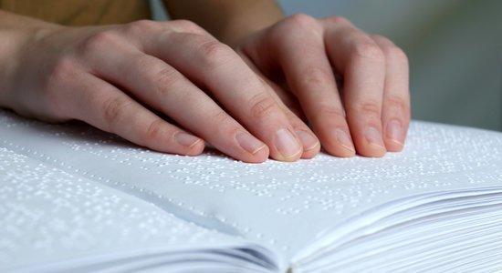 Mãos de uma mulher leem um livro em braille (foto: Shutterstock)