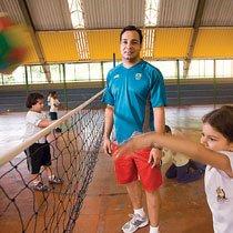 Na EMEB Marina Pires de Araujo, o professor Caio de Campos Busca propõe jogos de vôlei com regras e materiais adaptados. Ele pede que as crianças arremessem a bola por cima da rede com uma das mãos e depois com as duas. Quando nota que a tarefa é executada com facilidade, aumenta o desafio. Foto: Marina Piedade